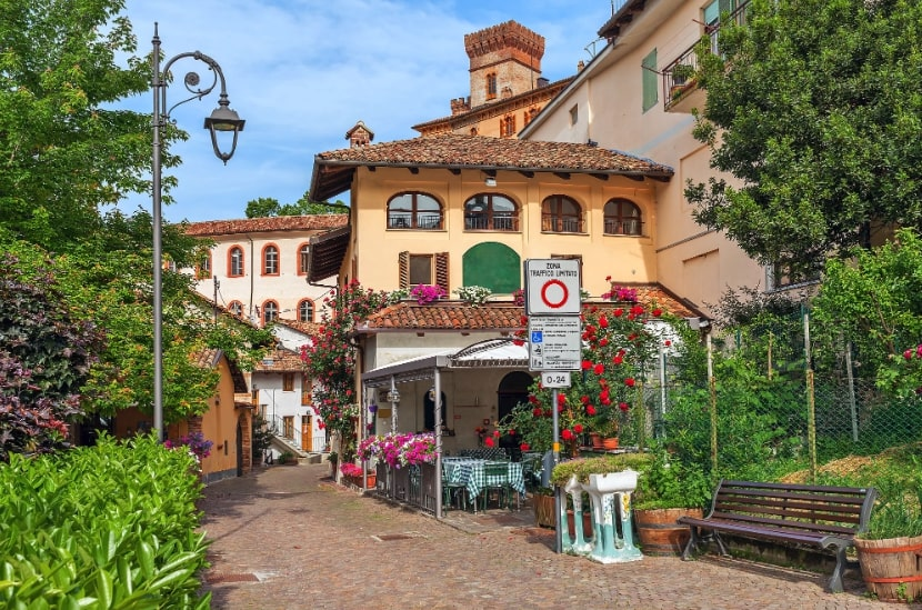 Narrow street among houses with flowers in town of Barolo in Piedmont, Northern Italy